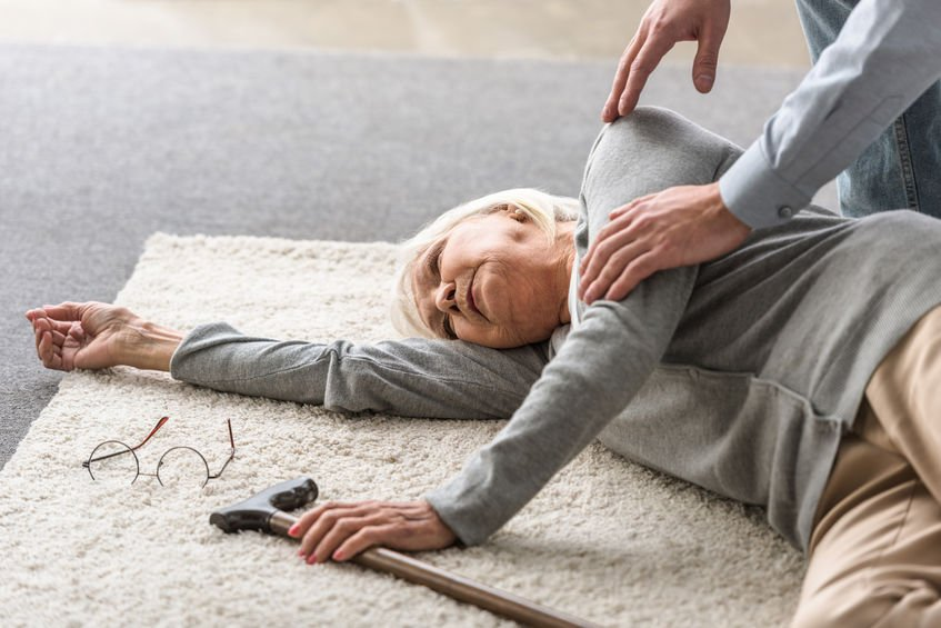 cropped view of man helping senior mother with heart attack fallen on carpet