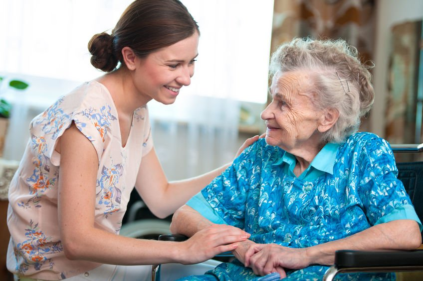 Senior woman with her caregiver at home